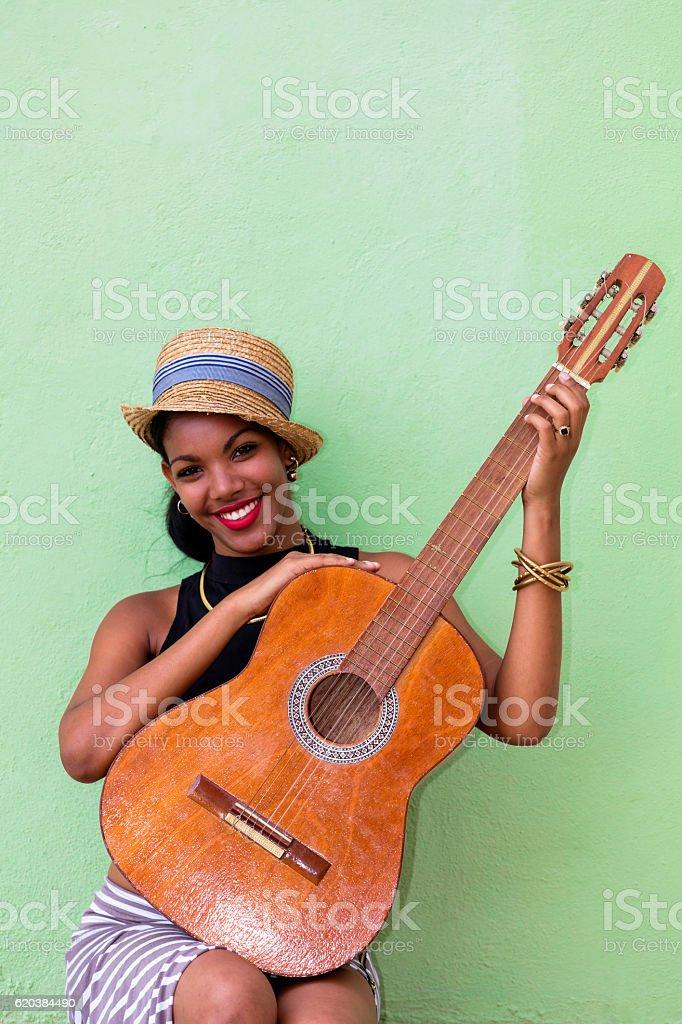 Beautiful young Cuban woman with guitar, Havana, Cuba stock photo