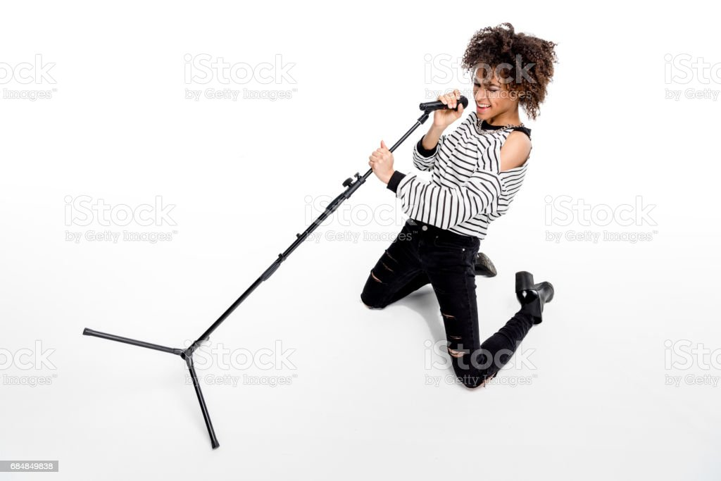 Beautiful young emotional heavy metal singer with microphone singing isolated on white stock photo