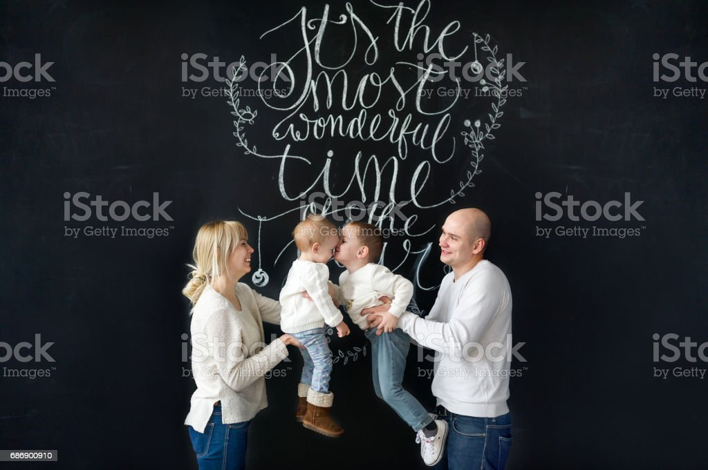 Beautiful young family happy with their kids. The brother kisses little sister. stock photo