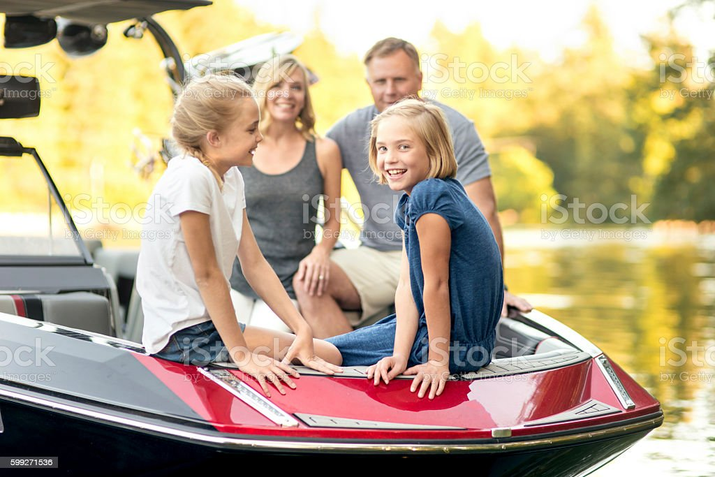 Beautiful young family sits in their ski boat stock photo