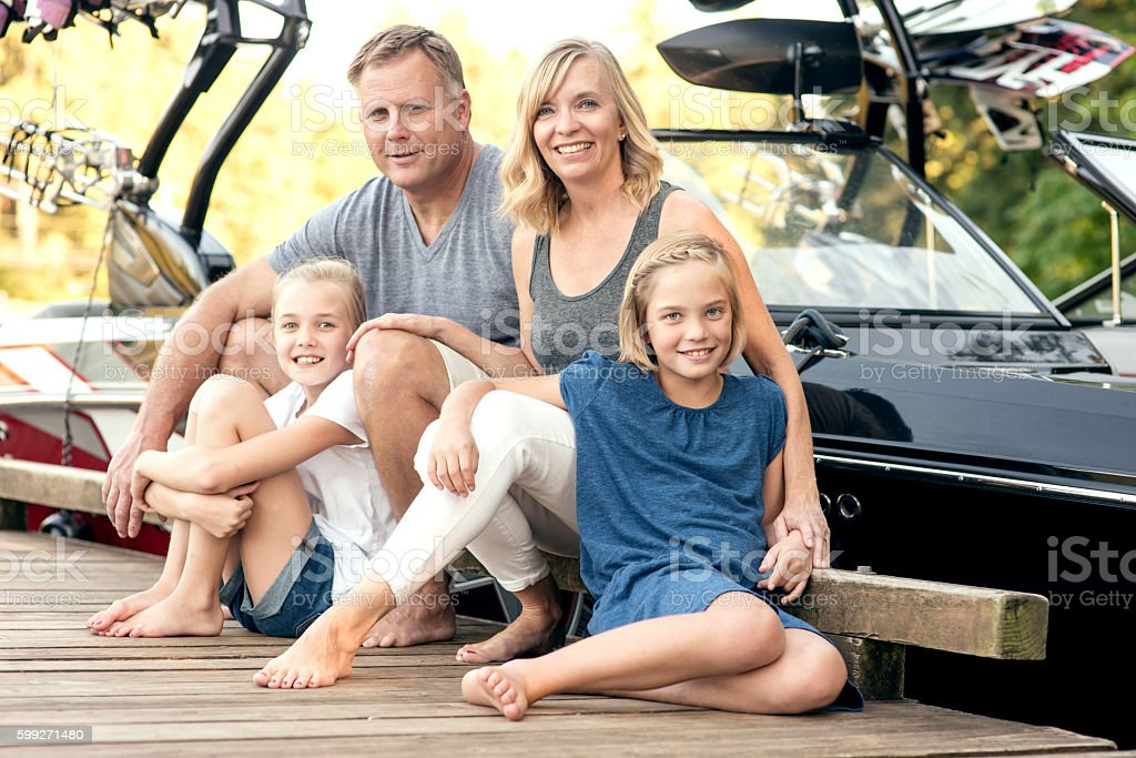 Beautiful young family sitting in front of their boat stock photo