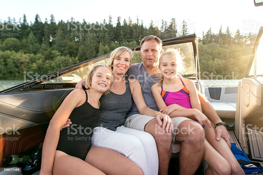 Beautiful young family snuggling in their ski boat stock photo