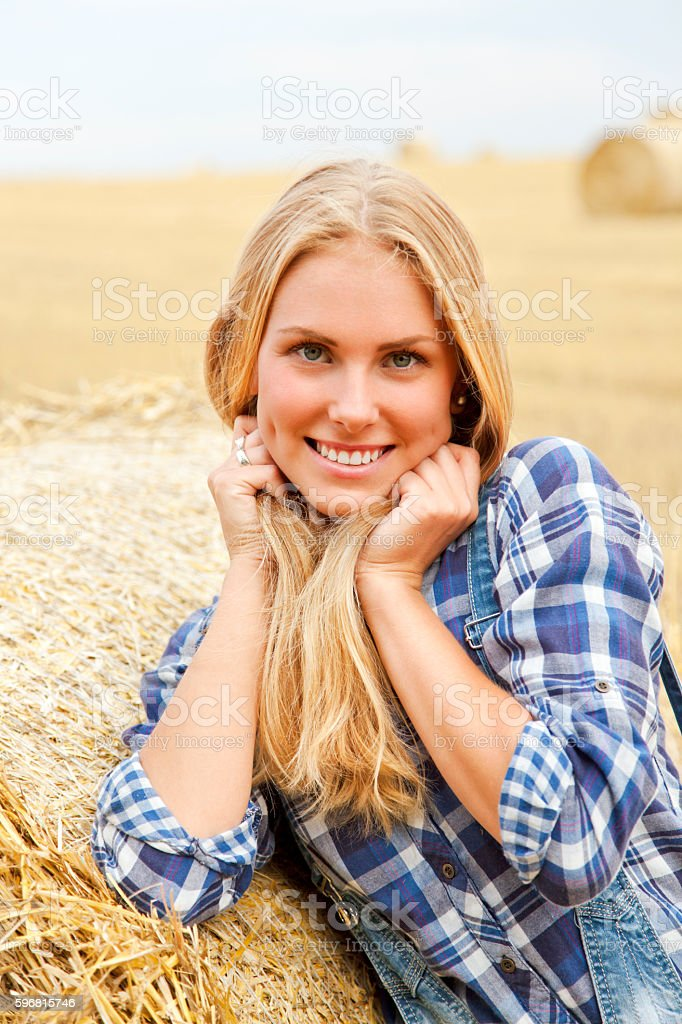 Beautiful young farmer wit cute smile behind bale of straw stock photo