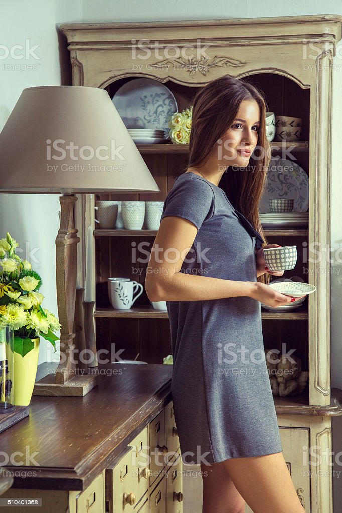 Beautiful young fashion model holding cup of tea. stock photo