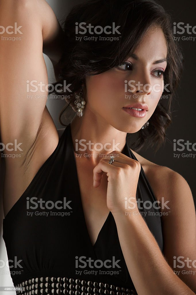 Beautiful young fashion model leaning against wall stock photo