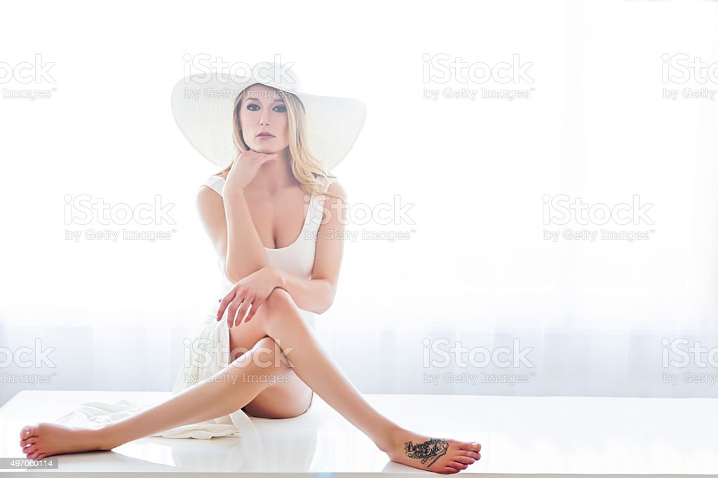 Beautiful young fashion model sitting on table stock photo