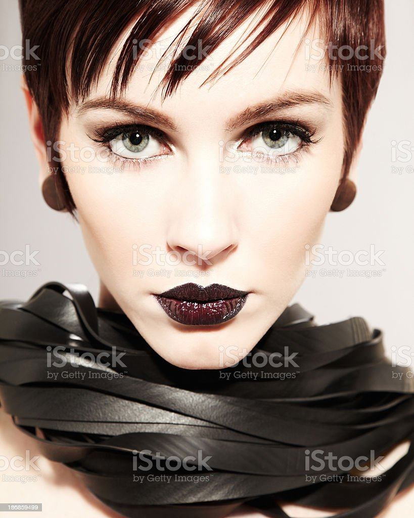 Beautiful young female dominatrix with rubber whip around her neck royalty-free stock photo