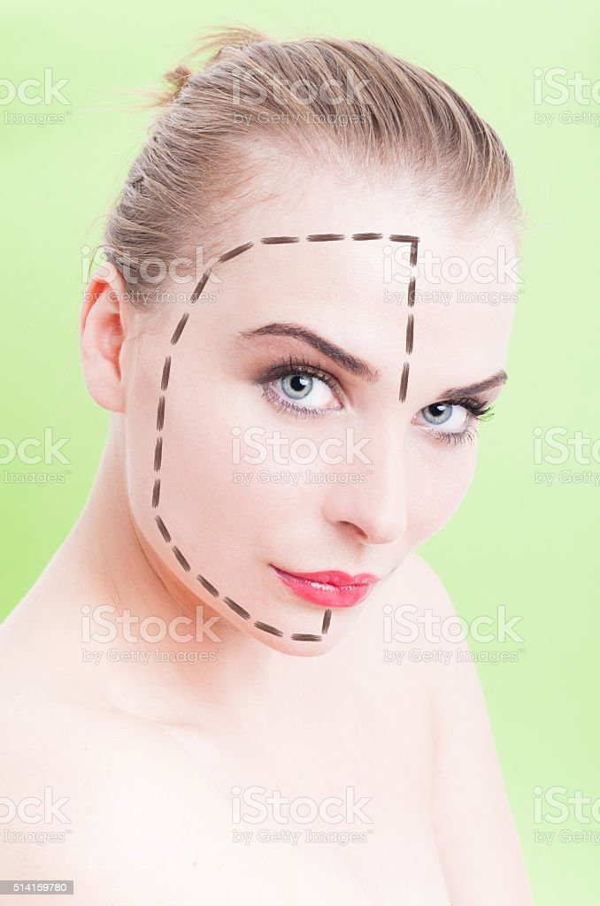 Beautiful young female face with facelift marks over green backg stock photo
