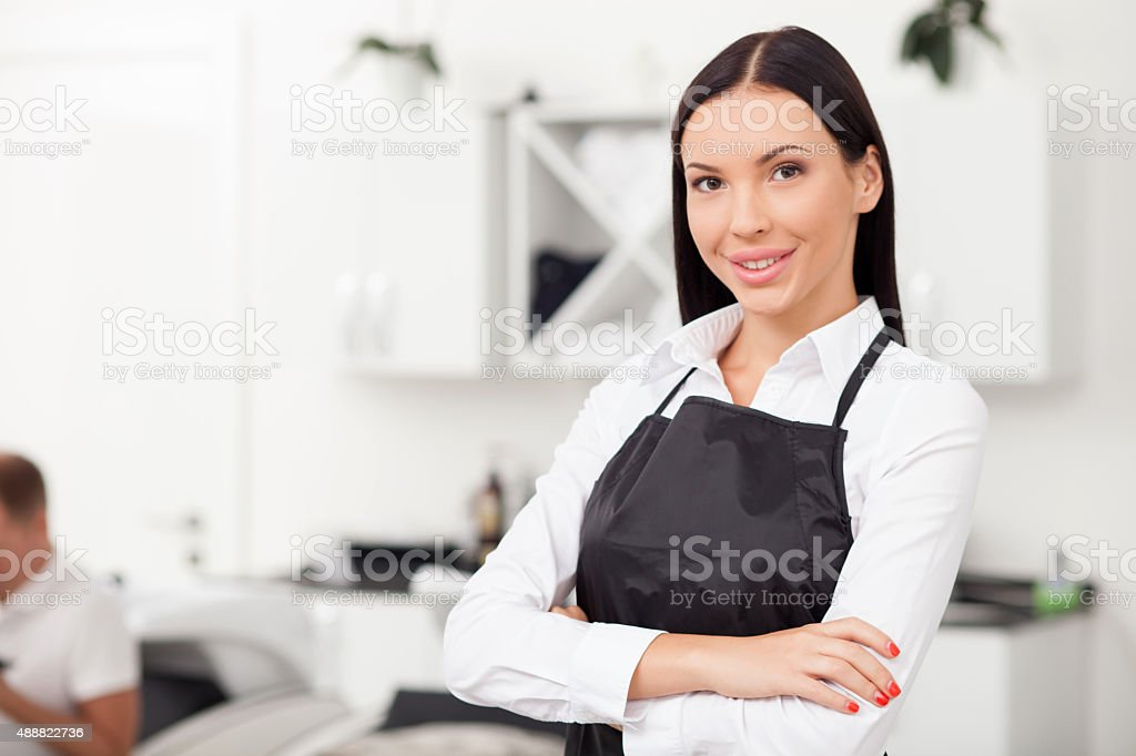 Beautiful young female hairstylist is working in salon stock photo