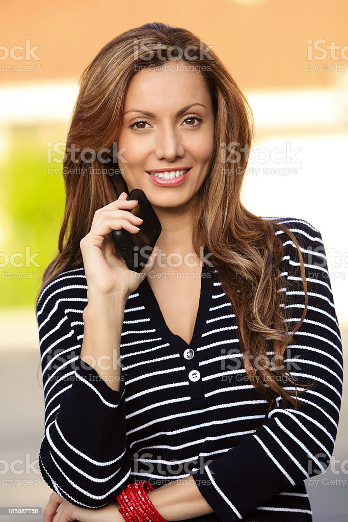Beautiful young female holding phone stock photo