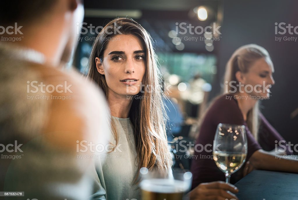 Beautiful young female looking at friend in bar stock photo