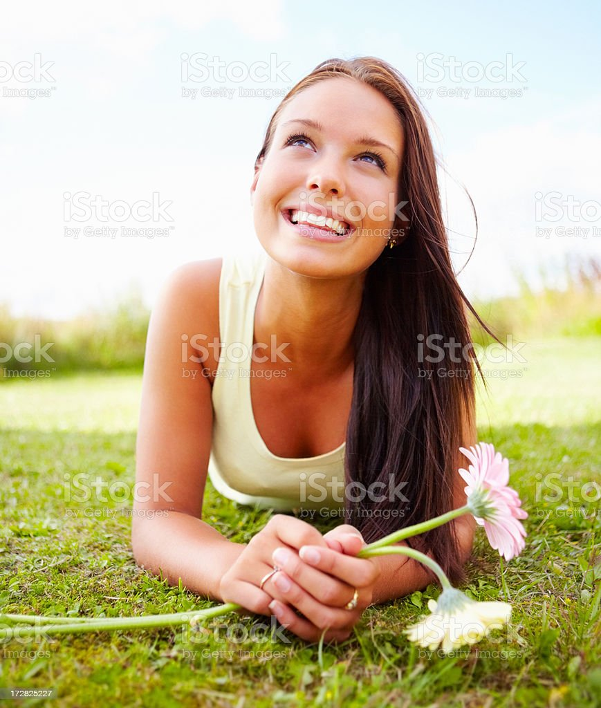 Beautiful young female looking upwards while lying at the park stock photo
