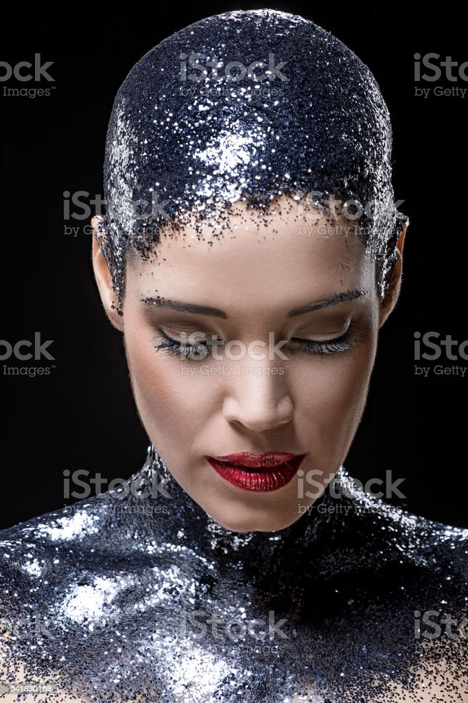 Beautiful young female model covered in black glitter in studio shoot stock photo