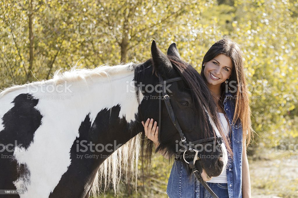 beautiful young female rider embracing her horse royalty-free stock photo