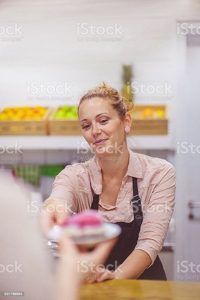 Beautiful young female small business owner serving organic cake stock photo