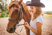 Beautiful young female walking and hugging with her horse outdoor