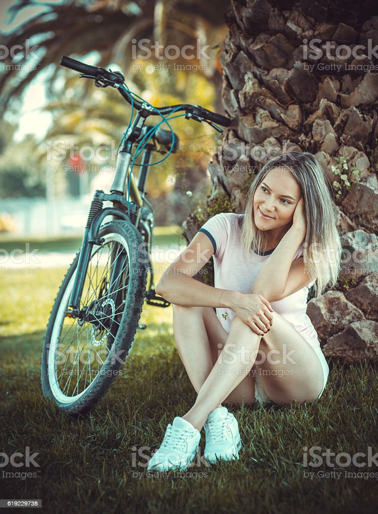 Beautiful young female with rent  bicycle sitting on the grass stock photo