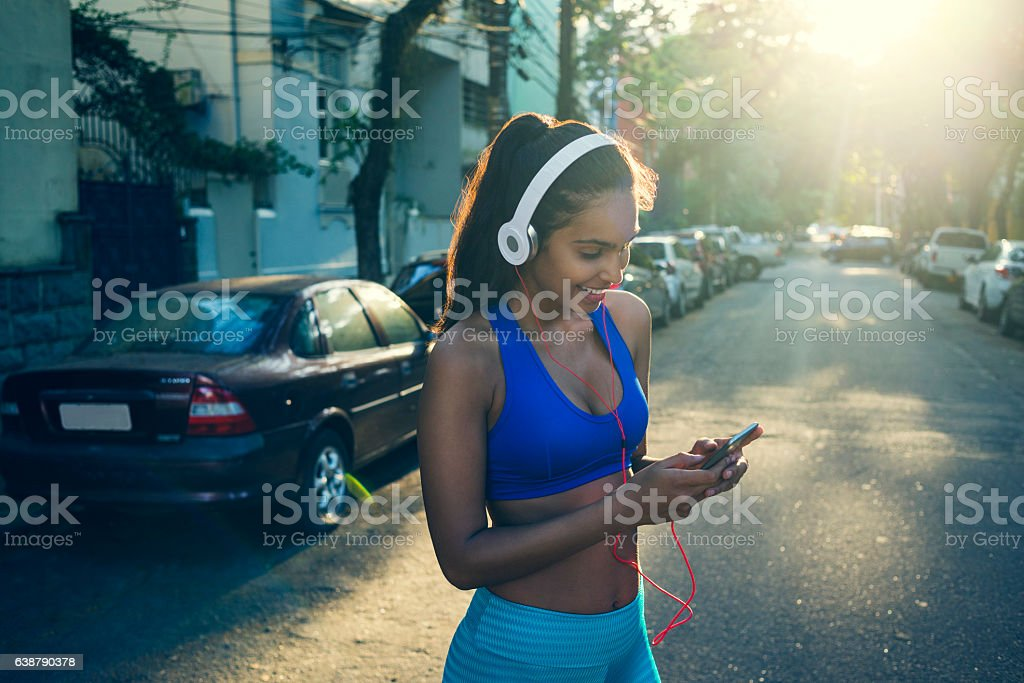 beautiful young fit woman using her smartphone after workout stock photo