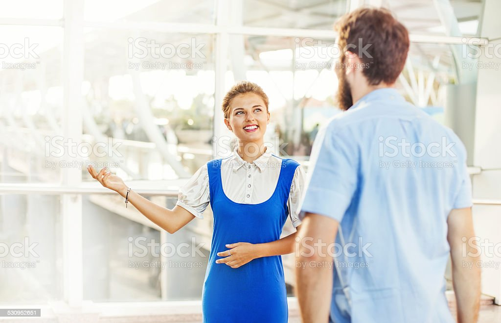 Beautiful young flight attendant in the airport explaining the way stock photo