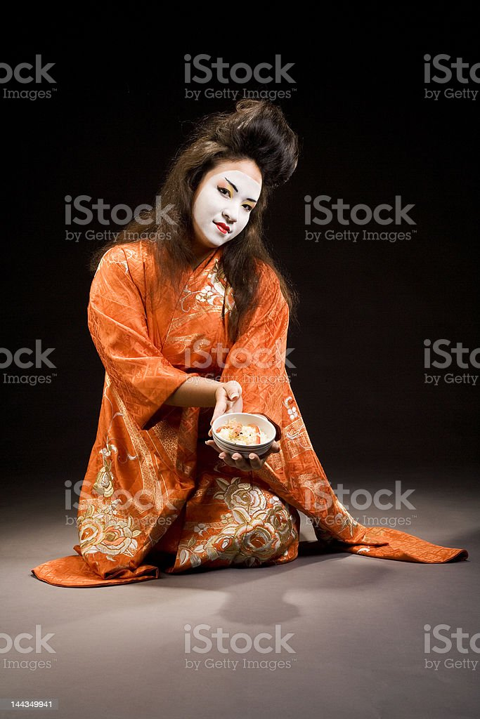 Beautiful young geisha woman in kimono with sushi royalty-free stock photo