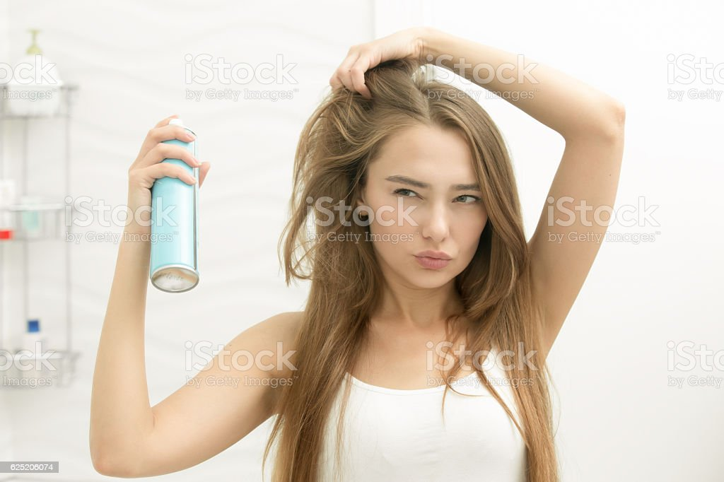 Beautiful young girl applying hair spray on her hair stock photo