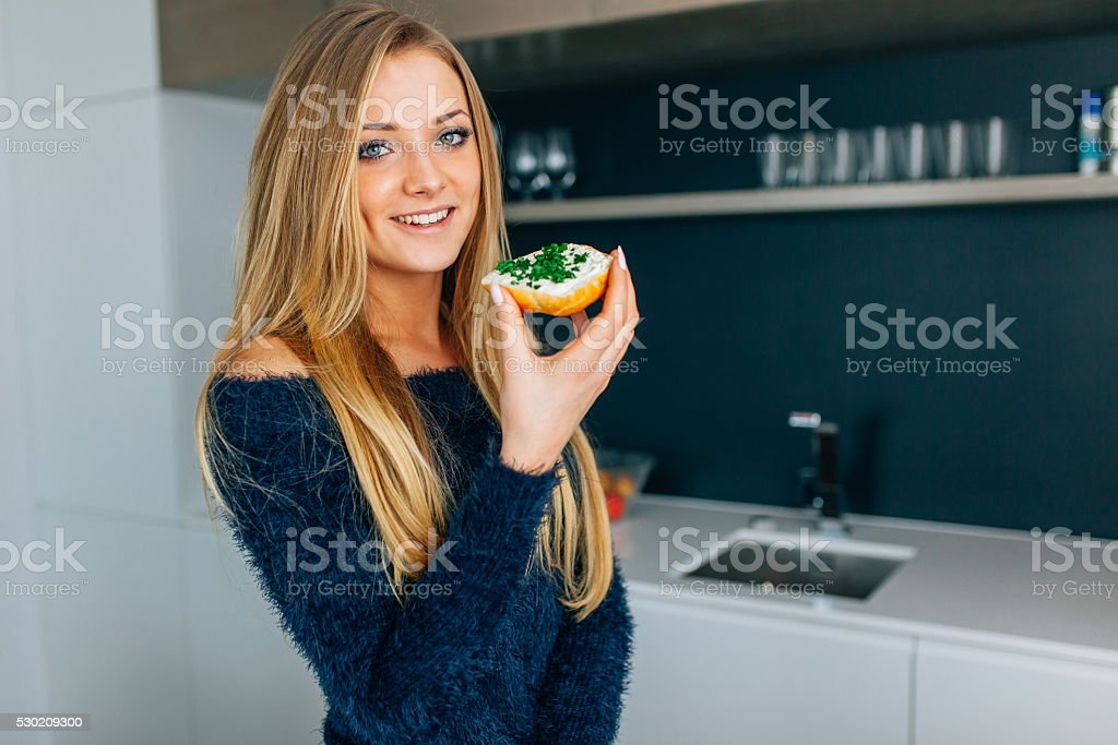 Beautiful young girl eating sandwiches in the kitchen. stock photo