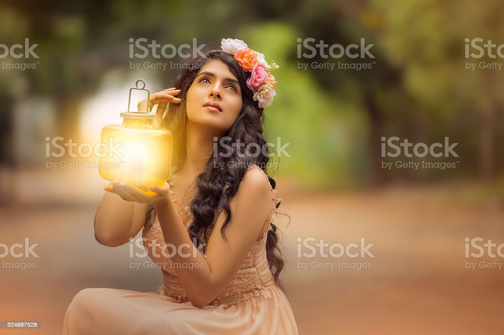 Beautiful young girl head with flower crown holding lamp stock photo