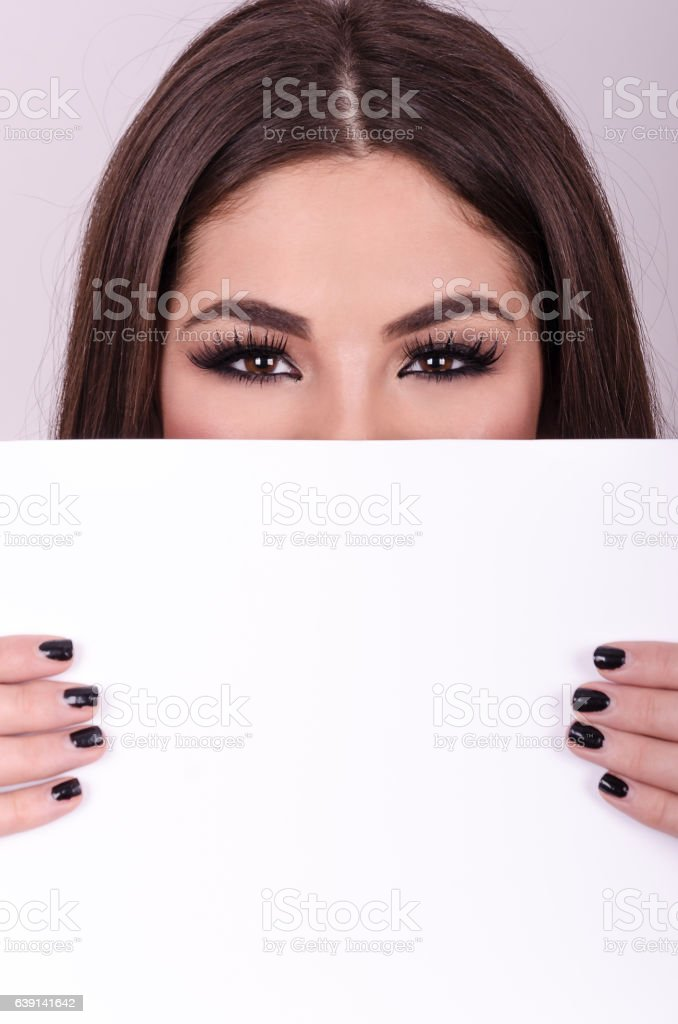 Beautiful young girl holding a paper over her mouth. stock photo