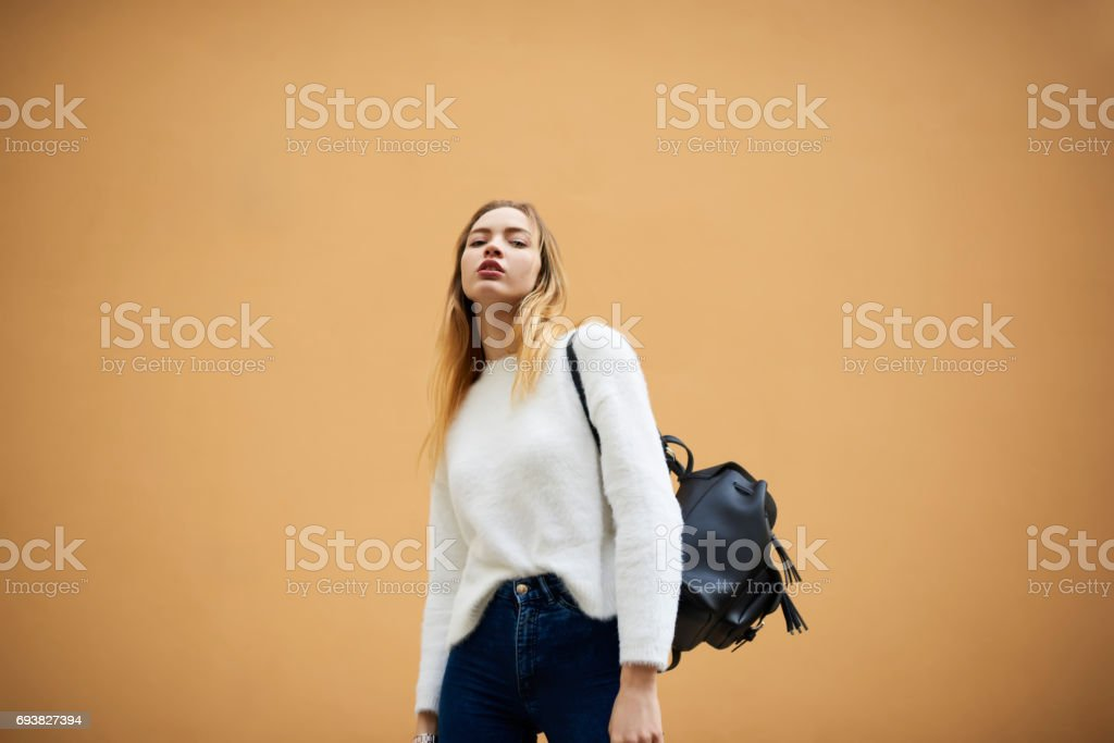 Beautiful young girl in a light sweater on a yellow wall background with copy space area stock photo