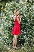 Beautiful young girl in cute red dress walking in the