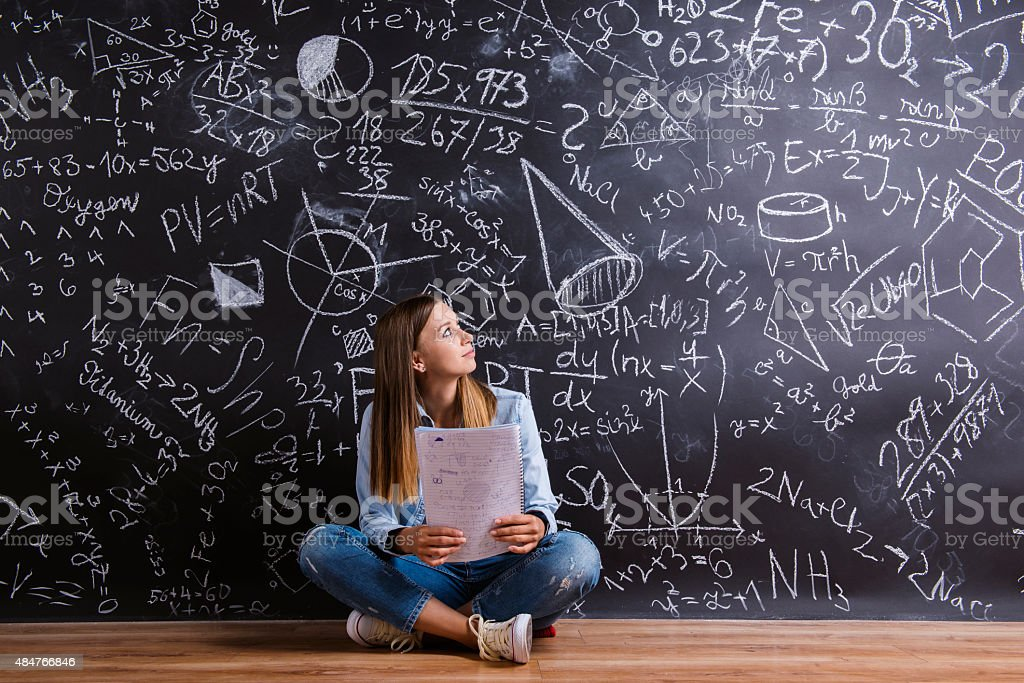 Beautiful young girl in front of blackboard stock photo