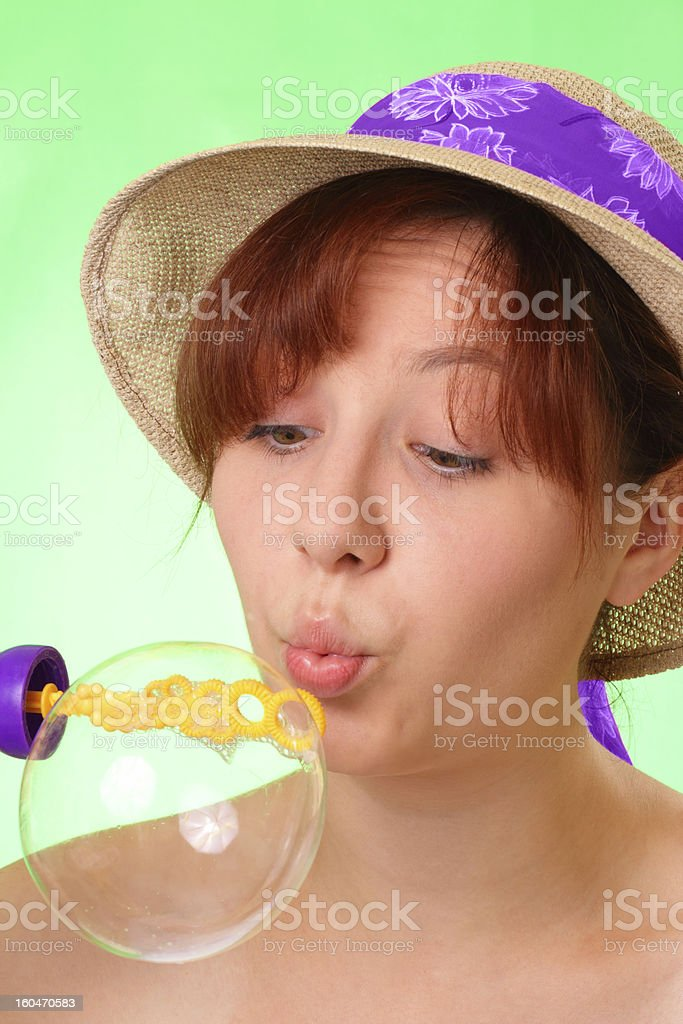 Beautiful young girl in hat blowing soap bubbles royalty-free stock photo
