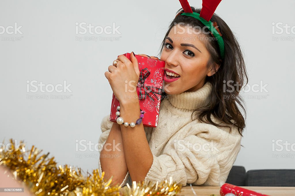 Beautiful young girl in reindeer horns with present. Christmas time stock photo