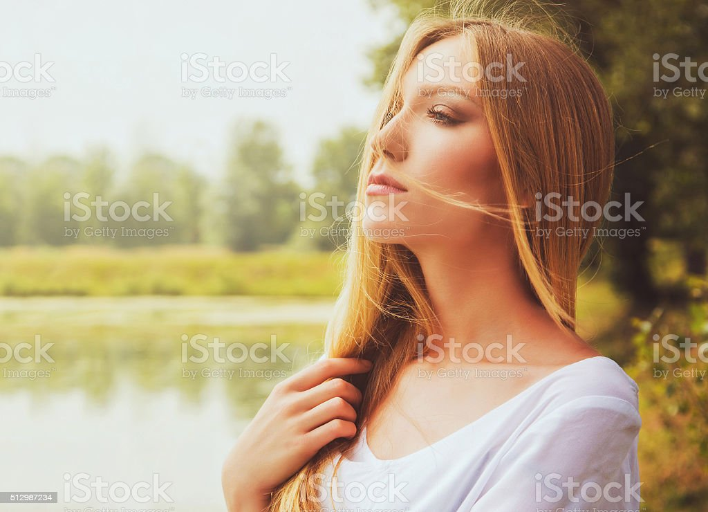 Beautiful young girl in white dress outdoor on lake shore stock photo