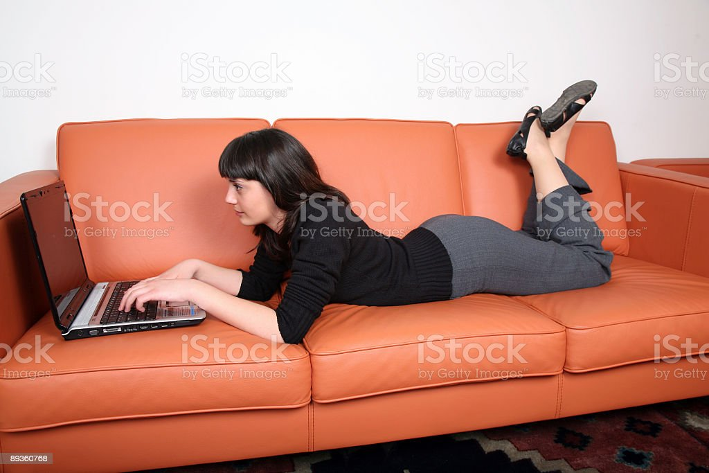 Beautiful young girl is lying by the computer royalty-free stock photo