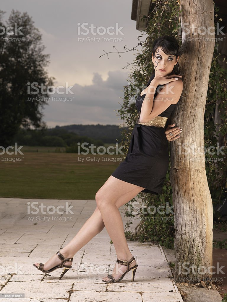 Beautiful young girl leaning against a pergola royalty-free stock photo