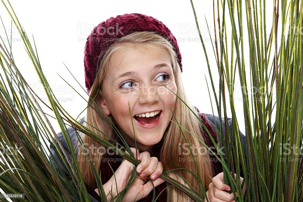 Beautiful young girl looking away at view through long grass royalty-free stock photo