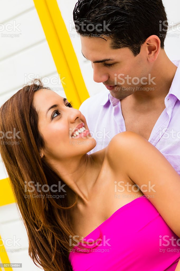 Beautiful young girl looking behind into eyes of man hugging stock photo