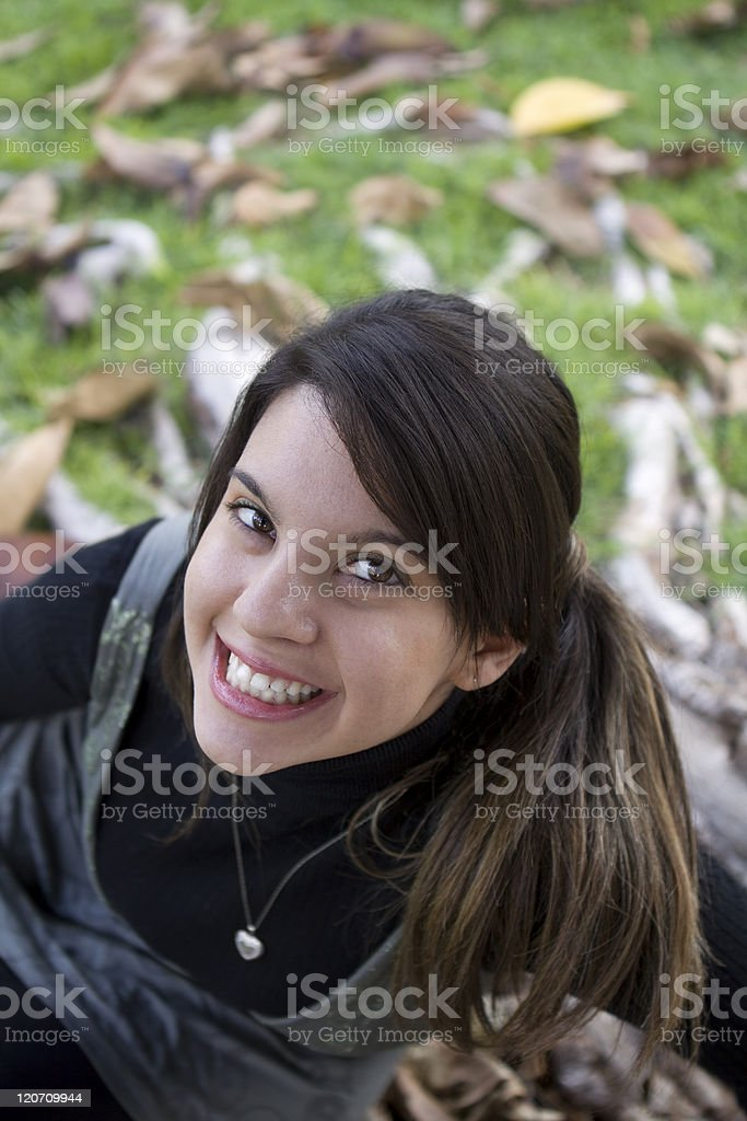 Beautiful Young Girl Looking Up Smiling in a Park royalty-free stock photo
