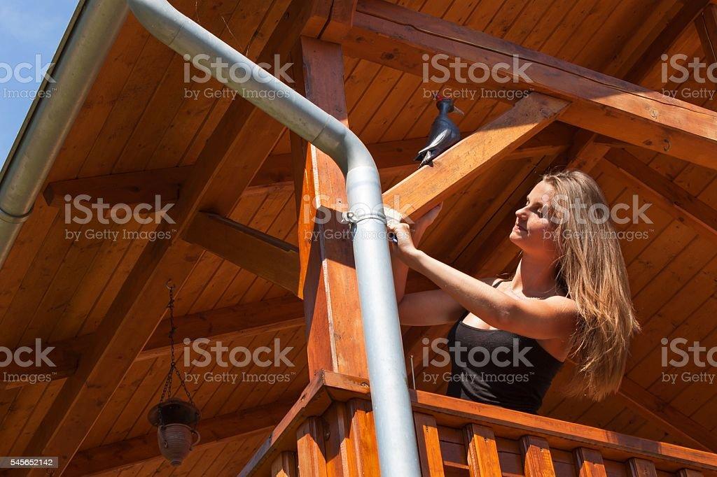 Beautiful young girl paints a wooden gazebo. stock photo