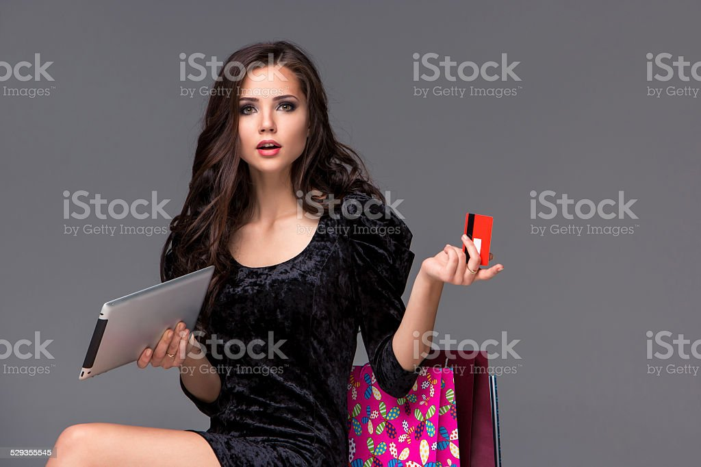 Beautiful young girl paying by credit card for shopping stock photo