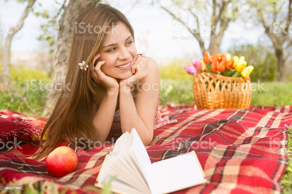 Beautiful young girl relaxing on picnic in the park stock photo