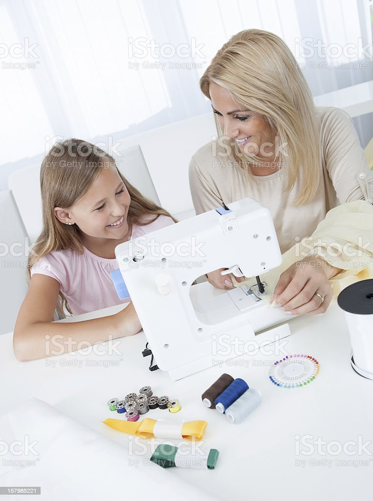 Beautiful Young Girl Sewing With Her Mother royalty-free stock photo