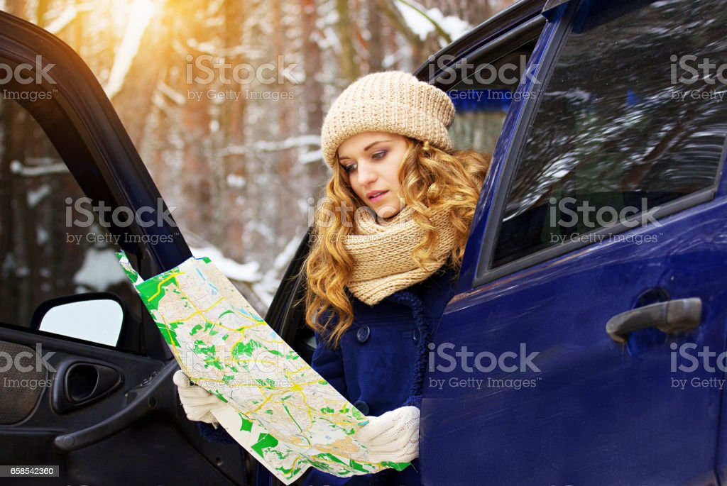 Beautiful young girl sits in a car and holding map in her hands, wearing blue jacket. Travel girl. stock photo