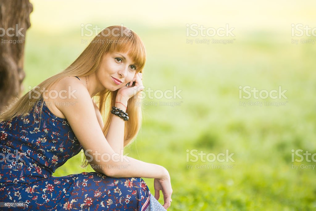 Beautiful young girl sitting against a tree on the background stock photo