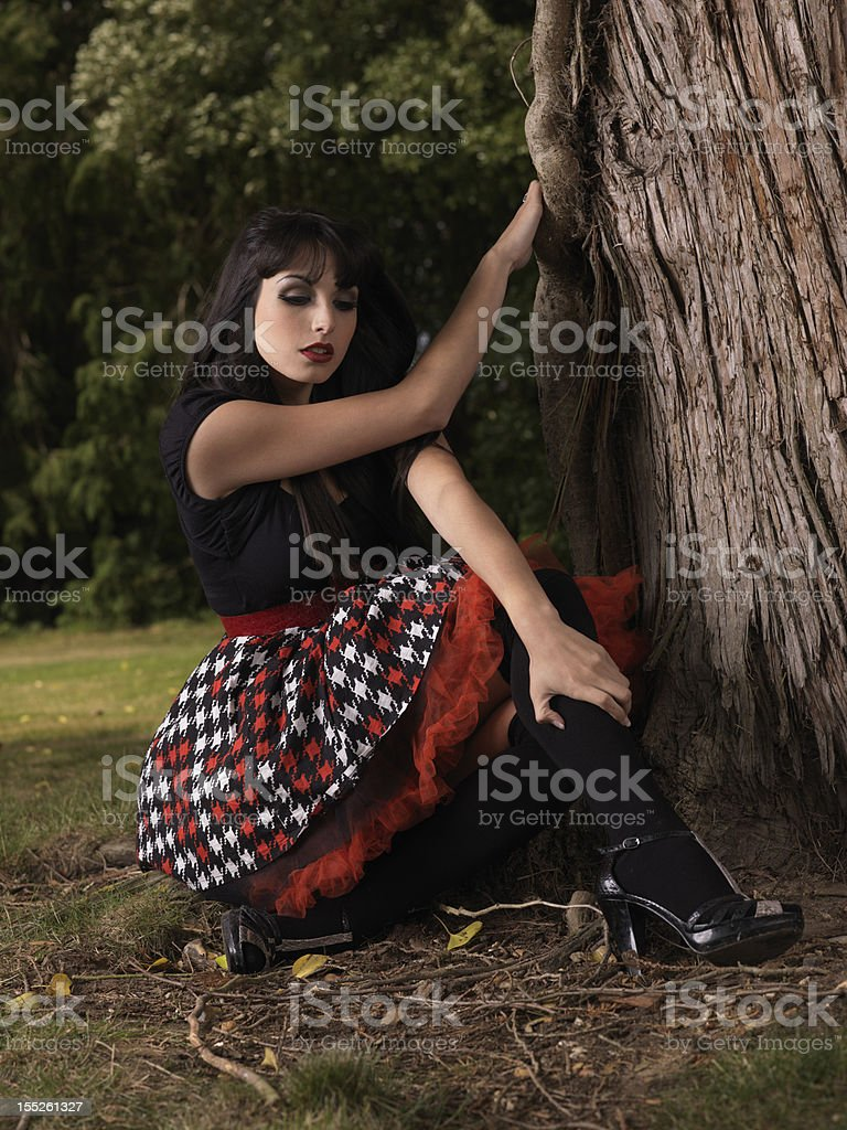 Beautiful young girl sitting next to tree royalty-free stock photo