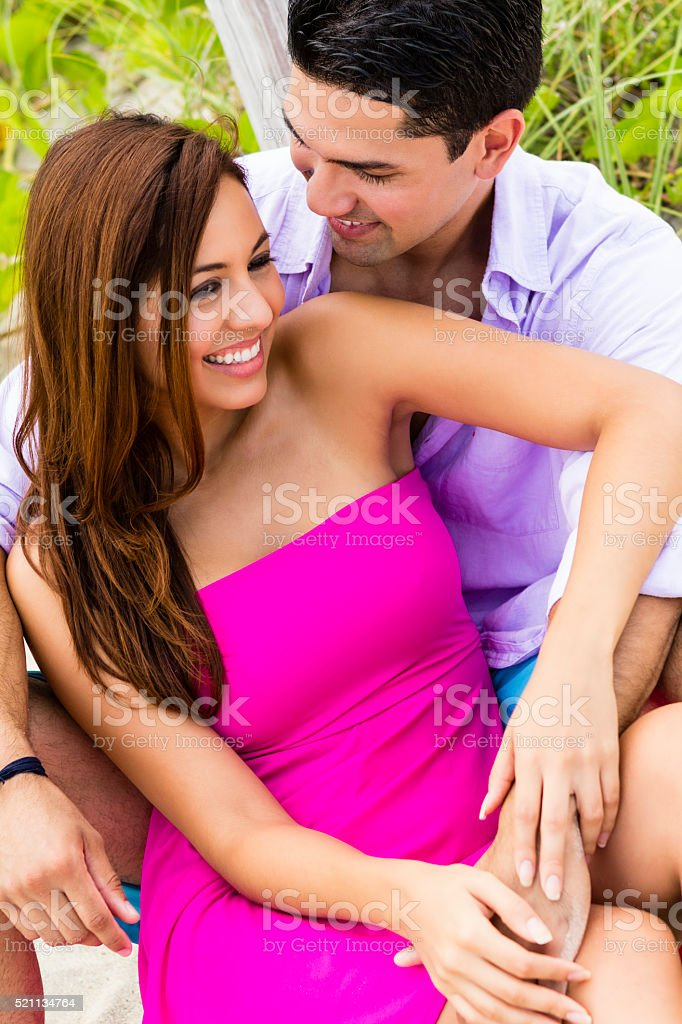 Beautiful young girl smiling and looking away; man touching stock photo