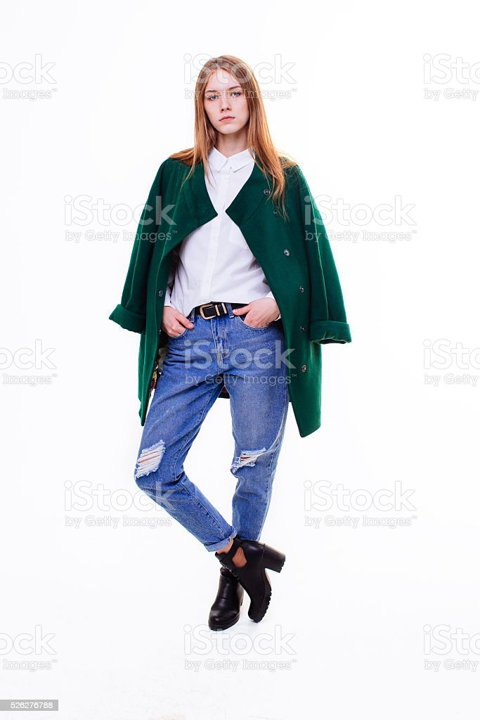 Beautiful young girl standing in coat. stock photo
