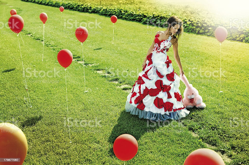 beautiful young girl standing in the middle of field balls royalty-free stock photo