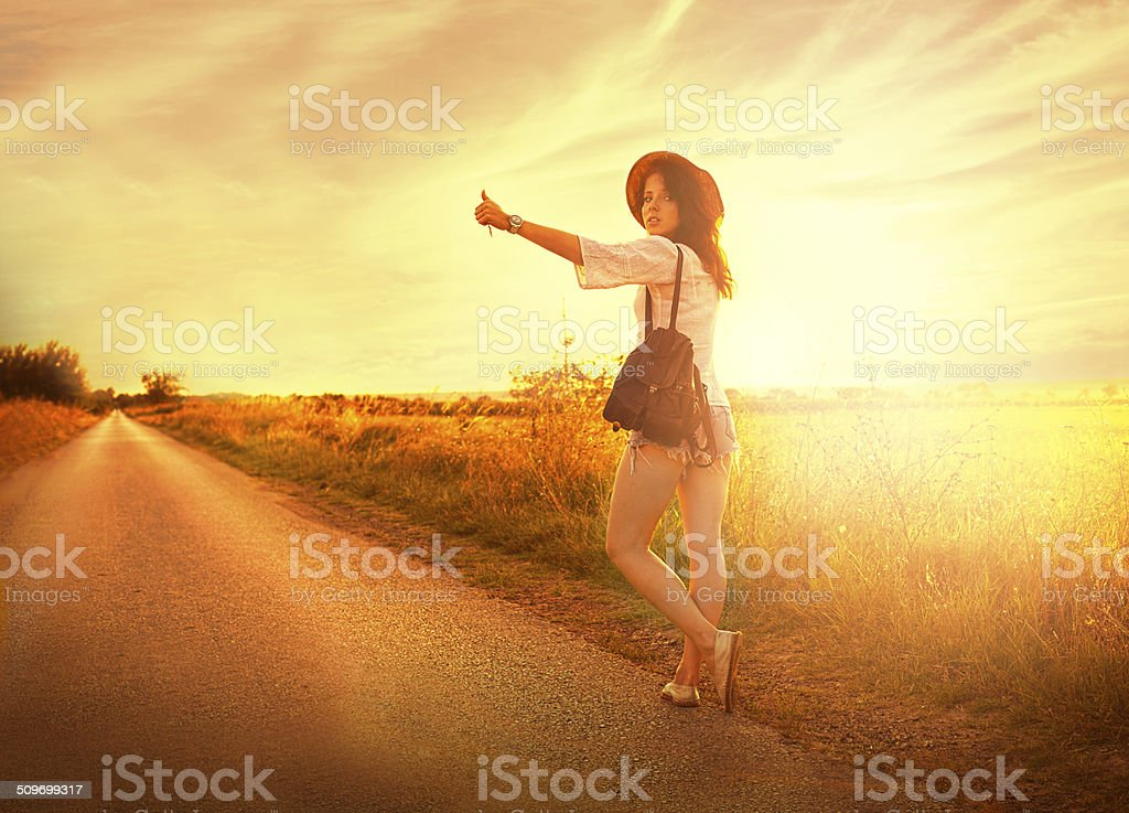 Beautiful young girl stops the car on road. stock photo